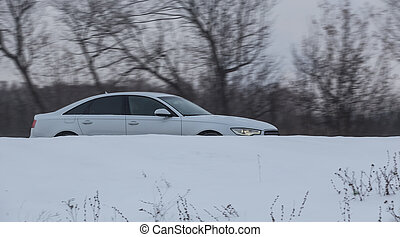 Car moves in the winter on a snowy road.