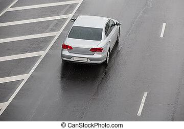 car moves on a wet multi-lane highway
