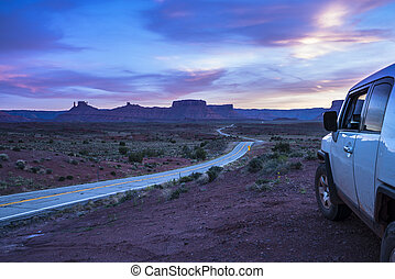 Car near an empty road leading to Moab Utah at Sunset Route...