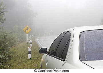 Car on a curve road in rainy and foggy weather