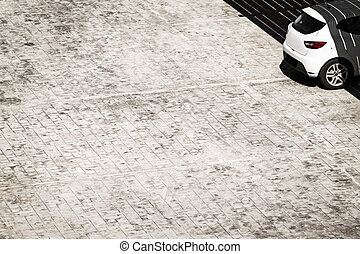 Car on a parking lot with grey tiled floor