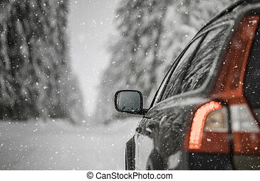 Car on a snowy winter road amid forests
