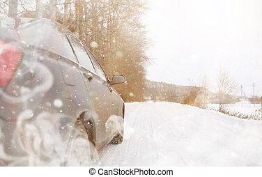 Car on a snowy winter road in fields.