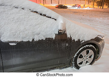 Car on a winter night under the snow