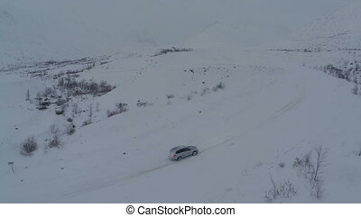 Car on heavy snowy road in mountains, aerial view