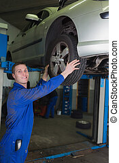 Car on hydraulic lift as mechanic examining tire in garage