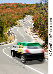 Car on road in national flag of afghanistan colors