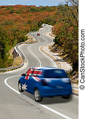 Car on road in national flag of australia colors