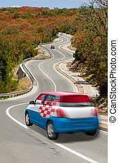 traveling car in national flag of croatia colors and beautiful road landscape for tourism and touristic adertising