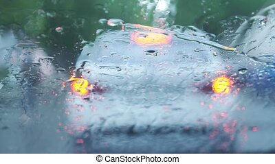 car on road Rain splatters car windshield during difficult...