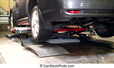 car on scissor lift moving down at auto service - repair,...