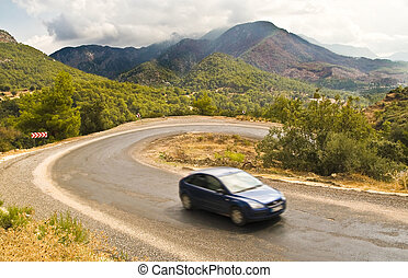 Car on serpentine road in mountains