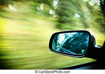 car on the road wiht motion blur background and rear view mirror