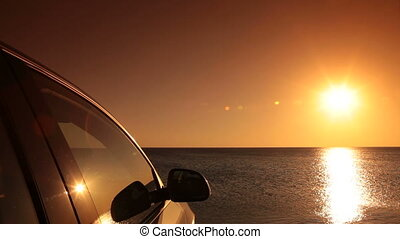 Car on the summer beach at sunset