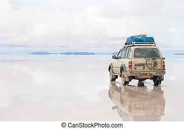 Car on the Uyuni Salar in Bolivia - Car on the reflected...