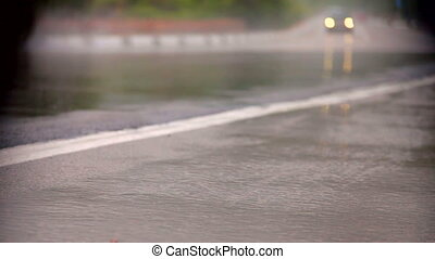 Car on Very Wet Road - A car splashes through a large puddle...