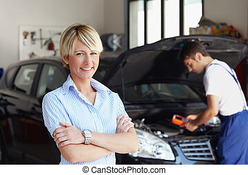 car owner - portrait of female client with arms folded in...