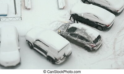 Car park with snow-covered cars in winter - View from the...