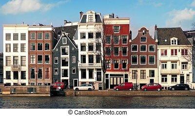 Car Passes Typical Dutch Houses - Car drives past parked...