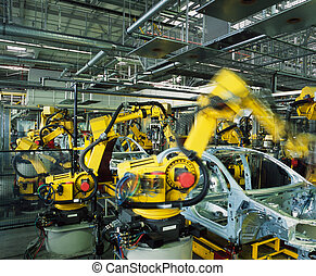 car production line - yellow robots welding cars in a ...