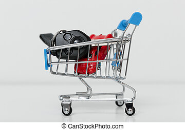 Car purchase concept. Red toy car and car keys in metal shopping cart