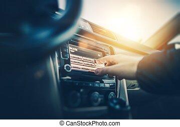 Car Radio Listening. Car Driver Changing Radio Stations on...