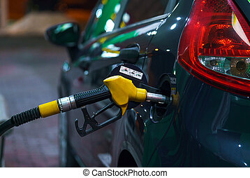 Car refueling on a petrol station at night