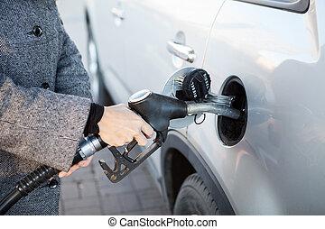 Car refueling on petrol station. Fuel pump with diesel, female hand inserting pistol in car petrol tank