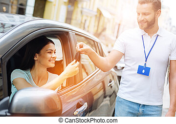 Car rental agency employee giving car keys to woman