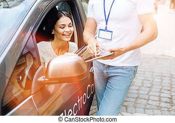 Car rental agency employee showing contract to the client