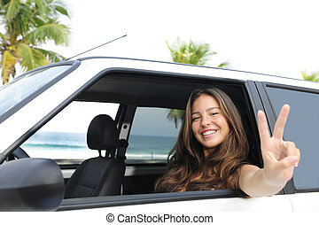car rental: happy woman in her car near the beach showing...