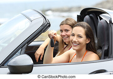 Car renters holding a key looking at you