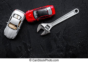 Car repair concept. Wrench near car toys on black background top view copyspace
