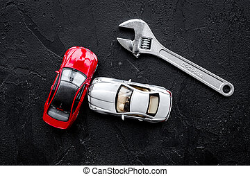 Car repair concept. Wrench near car toys on black background top view