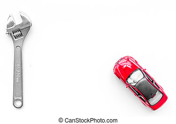 Car repair concept. Wrench near car toys on white background top view copyspace