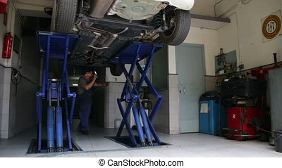 Car Repair Looking for Damage - Mechanic checking a car...