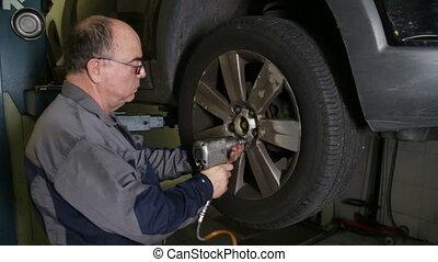 Car Repair Mechanic Changing Wheel - Mechanic changes a car...