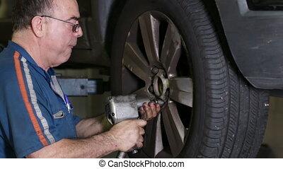 Car Repair Mechanic Mounts Wheel - Mechanic mounting a car...