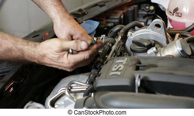 Car Repair Removing the Oil Filter - A repairman changing...