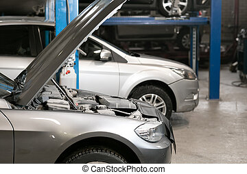 car repair station. cars stand in small service and repair one car.