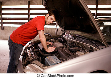 Car Repair - A male looking under the hood of a car
