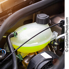 Car reservoir for filling coolant. Yellow antifreeze in the ...
