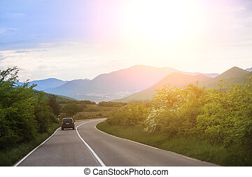 car rides along a country road in the mountains