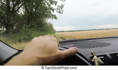 Car rides along country road between fields, view from...