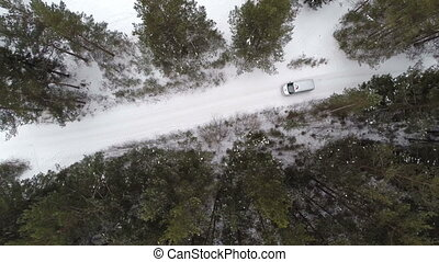 Car rides by road at winter day. Aerial view