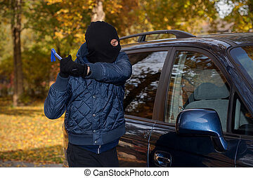 Car robbery - A masked man robbing a car by breaking the...