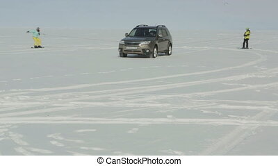 Car rolls skiers on ice of Lake Baikal. - Car rolls skiers...