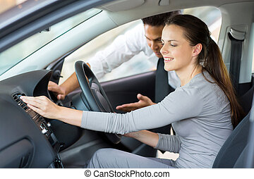 car sales consultant showing a new car to a young woman