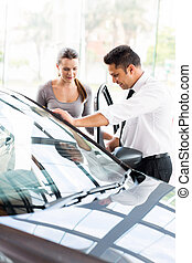 car sales consultant showing a new car to potential buyer -...