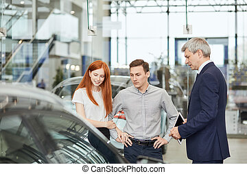 Car Business, Car Dealership, Customers and Rep Concept. Salesman talking to a young couple at the dealership showroom.